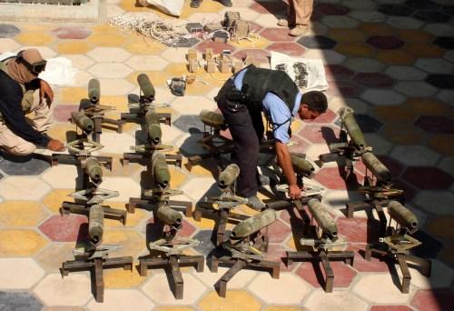عنصرا شرطة عراقيّان يجمعان صواريخ ضُبطت في مدينة الحلّة أمس (رويترز)
