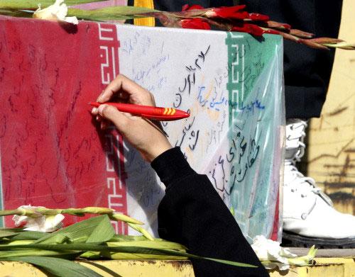 إيرانيّة تكتب على نعش رمزي لجنود قُتلوا خلال الحرب مع العراق (فاهيد سالمي ـ أ ب)
