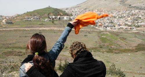 سوريّة تلوّح لأقاربها في الجزء المحتلّ من هضبة الجولان (خالد الحريري ـــ رويترز)