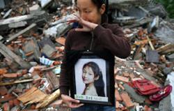 صينيّة تحمل صورة ابنتها التي توفّيت في زلزال سيشوان أمس (دايفيد غوتنفلدر ـــ أ ب)