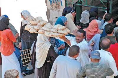 مصريون ينتظرون في طوابير على باب أحد المخابز في مصر أمس (الأخبار)