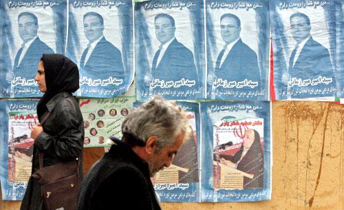ايرانيان يسيران امام صور مرشحي الانتخابات في طهران امس (ا ب)