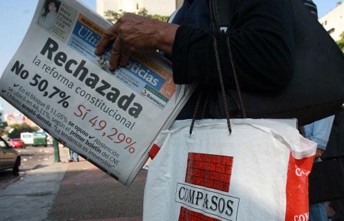 فنزويليّة تحمل صحيفة عنونت رفض التعديلات الدستوريّة في كراكاس أمس (يوري كورتيز ـ أ ف ب)