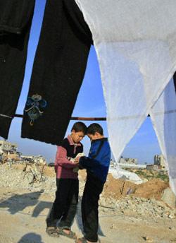 فلسطينيان يجمعان أحجار المباني المهدمة بفعل الحرب في جباليا الأسبوع الماضي (محمد عبد ــ أ ف ب)