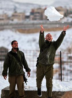 جنديان إسرائيليان يلهوان بالثلوج عند جبل حرمون في الجولان السوري المحتل (أرييل شاليط ــ أ ب)