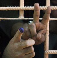 سجينان عراقيان يرفعان أصابعهما بعد اقتراعهما في عملية التصويت الخاص التي بدأت أمس (محمد سواف - أ ف ب)