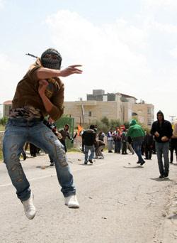 فلسطيني يلقي حجراً على نقطة تفتيش إسرائيلية قرب بيت لحم في الضفة الغربية أمس (موسى الشاعر ــ أ ف ب)