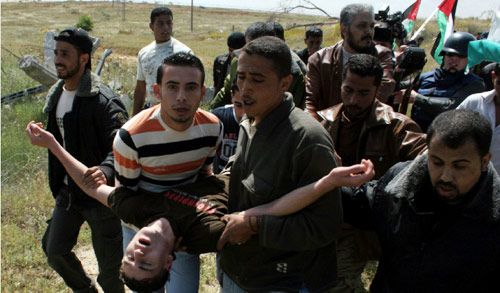 فلسطينيون يحملون جريحاً خلال مسيرة ليوم الأرض في غزة أمس (أشرف عمرا ــ أ ب)
