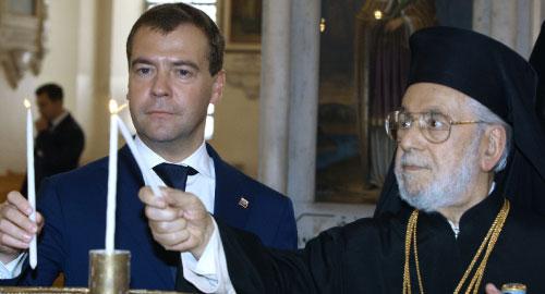 بطريرك انطاكية وسائر المشرق للروم الأرثوذكس ومدفيديف يضيئان الشموع في الكاتدرائية المريمية أمس (أ ب)