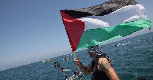 فلسطيني يلوّّح بعلم بلاده استعداداً لوصول «أسطول الحرية» أمس (محمود حمص ـ أ ف ب)