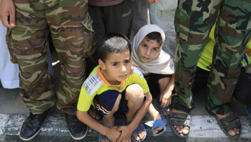 طفلان يشاهدان تظاهرة مناهضة لإسرائيل في غزة أمس (محمد عبد ــ أ ف ب)