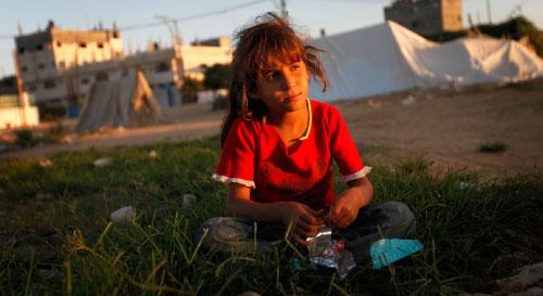 طفلة غزيّة تجلس خارج خيمتها بعدما دمرت إسرائيل منزلها (لفتارس بكاراتس ـ أ ب)