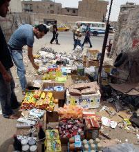 عراقي يتفقد البضائع من القواعد الاميركية في سوق شعبي (سعد شلش ــ رويترز)