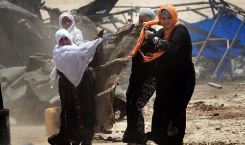 نسوة يتساعدن في ازالة قطعة من الصفيح بعدما هدمت القوات الإسرائيلية منازلهن في العراقيب (مناحيم كاهانا ــ أ ف ب)