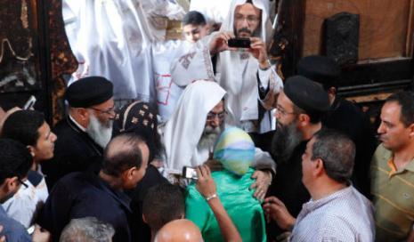 مسلمة تُعانق كاهناً تعبيراً عن حزنها للاشتباكات الطائفية (أسماء وجيه ــ رويترز)