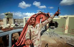 عنصر من «الانتقالي» خلال هدم مجمّع باب العزيزية في طرابلس أمس (صهيب سالم ــ رويترز)