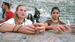 ردنية وسائحة دنماركية تضيئان شمعتين في موقه الاعتداء في المدرج الروماني في عمان أمس (أ ب)