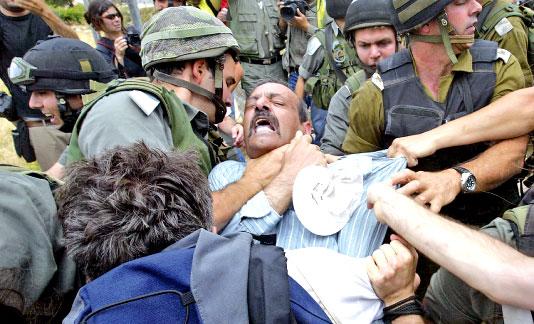 جندي اسرائيلي «يخنق» متظاهراً ضدّ الجدار العازل جنوبي بيت لحم أمس (موسى الساهر - أ ف ب)