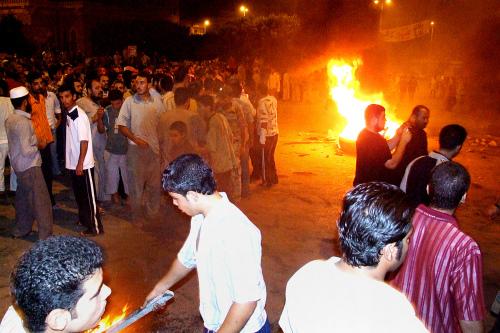 متظاهرون أمام مركز الحزب الحاكم في العريش أمس (أشرف سويلمان - أ ب)