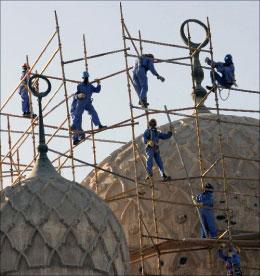 عمال آسيويون يقومون بترميم قبّة مسجد في دبي (كريم صاحب - أ ف ب)