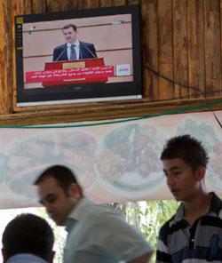 لاجئون سوريون يتابعون خطاب الأسد بمقهى في تركيا (فاديم غيردا ــ أ ب)