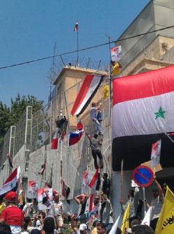خلال رفع الأعلام السورية على مبنى السفارة الأميركية لدى دمشق يوم الاثنين (أ ب)
