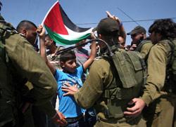 طفل فلسطيني يواجه جنود الاحتلال في كفر قدوم أمس (جعفر عشتيه - أ ف ب)