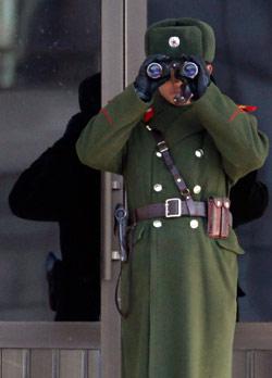جندي كوري شمالي يراقب الحدود بين الكوريتين في قرية بانمونجوم المنزوعة السلاح (جو يونغ هاك - رويترز)