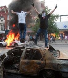 متظاهران مناهضان لقمة العشرين يحرقان سيارتين في تورونتو أول من أمس (ريان ريميرز ــ أ ب)