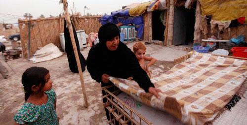 عراقية تعد الفراش خارج المنزل بسبب انقطاع التيار الكهربائي في بغداد أمس (هادي مزبان ــ أ ب)