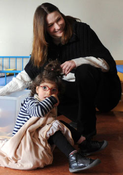 كارلا بروني خلال جولة على مدرسة لذوي الاحتياجات الخاصة في باريس (رويترز)