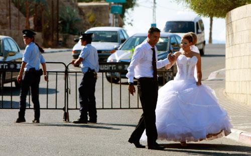 عروسان من عرب إسرائيل يسيران بمحاذاة نقطة تفتيش إسرائيلية في عكا أول من أمس (عمار عواد - رويترز)