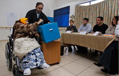 إسرائيلية تنتخب في مركز للاقتراع في مستوطنة في الضفة الغربية أمس (دان باليتي - أ ب)