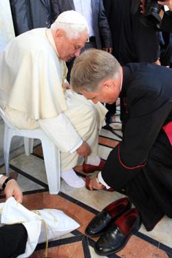 البابا ينتعل حذاءه لدى خروجه من مسجد قبة الصخرة أمس (عطا عويصات - أ ف ب)