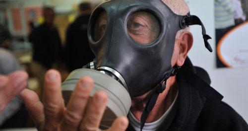 اسرائيلي يجرّب قناعاً واقياً من الغاز في تل ابيب الأسبوع الماضي (يهودا رايزر - أ ف ب)
