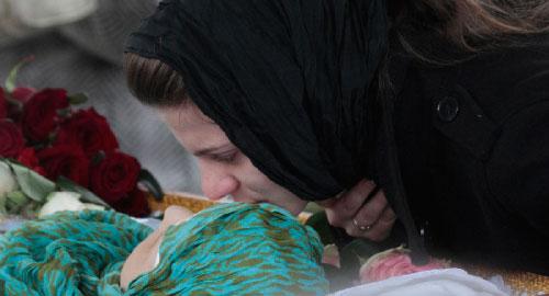 روسية تُقبّل قريبتها خلال تشييعها في موسكو أمس (ألكسندر ناتروسكين ــ رويترز)