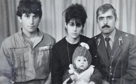 الطفل تاميرلان مع والديه وعمّه في صورة من أرشيف العائلة (رويترز
