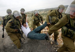جنود إسرائيليون يعتقلون متظاهراً فلسطينياً في بلعين أمس (فادي قاروري - رويترز)
