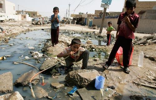أطفال يشربون مياهاً آسنة في مدينة الصدر (كريم كاظم ـــ أ ب)
