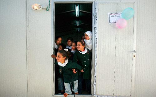 تلميذات فلسطينيات داخل مستوعب بعدما دمرت مدرستهن في بيت لاهيا أمس (سهيب سالم ــ رويترز)