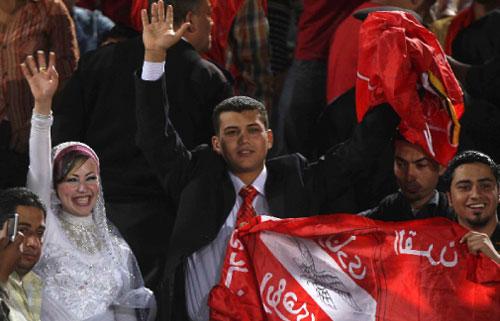 ثنائي مصري يحتفل بزواجه في مباراة لكرة القدم بين الأهلي والزمالك في القاهرة أول من أمس (عمر عبد الله - رويترز)