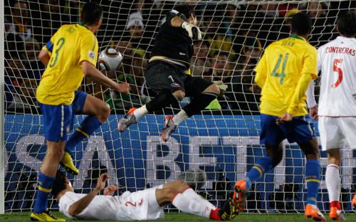 البرازيلي جوان (4) يراقب كرته وهي تخترق مرمى الحارس التشيلي برافو (أندريه بينير ـ أ ب)
