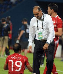 مدرب تونس طرابلسي يواسي لاعبه خليفة بعد الخروج من البطولة (أ ف ب)