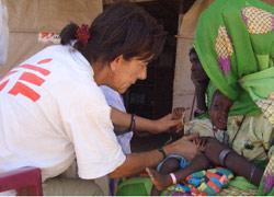 متطوعة في منظمة «أطباء بلا حدود» تقدم الرعاية الطبية لأحد أطفال دارفور (أرشيف ــ مارتين بروغتون)