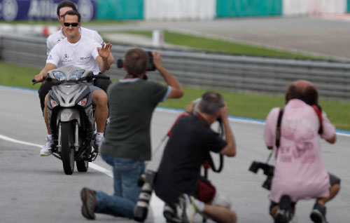 مصوّرون يلتقطون صوراً لميكايل شوماخر خلال جولةٍ له على حلبة سيبانغ (فيفيك براكاش ـ رويترز)