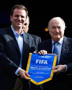 السويسري جوزف بلاتر يقدّم شعار الفيفا الى عمدة مدينة ريو دي جانيرو سيرجيو بايس أمس (فيليبي دانا ــ أ ب)