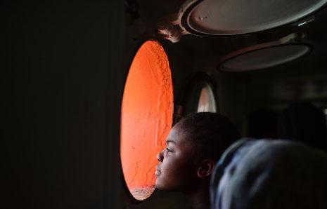 فتاة تنظر من شباك سفينة النجاة «أكواريوس» أثناء وصول أكثر من 380 مهاجراً إلى مرفأ كاليغري في جزيرة ساردينيا الإيطالية، بعد يومين من إنقاذهم بالقرب من السواحل الليبية. (غابريال بويس ــ أ ف ب)