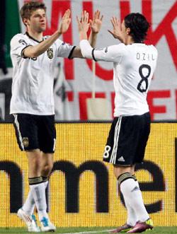 توماس مولر يتلقى تهنئة مسعود أوزيل (8) بعد تسجيله أحد هدفيه في مرمى كازاخستان (فرانك أوغستين ـ أ ب)