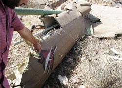 مقاوم يشير إلى حطام مروحية إسرائيلية أسقطتها المقاومة (وائل اللادقي)