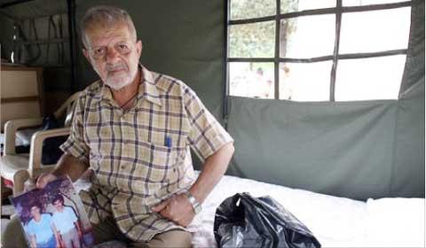 يحمل صورة ولديه داخل خيمة «سوليد» (مروان طحطح)